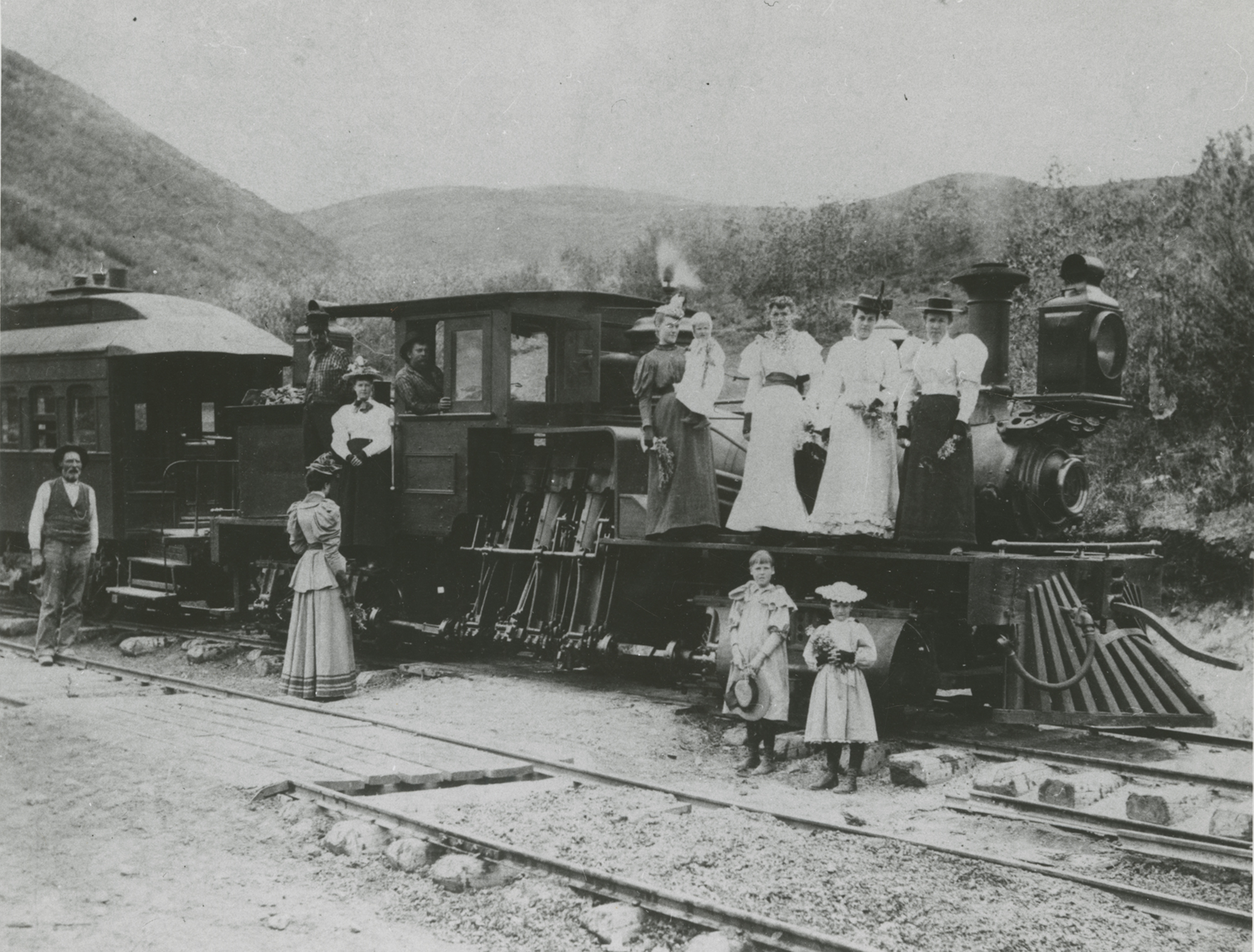 A historical photo of several women and children near a train.