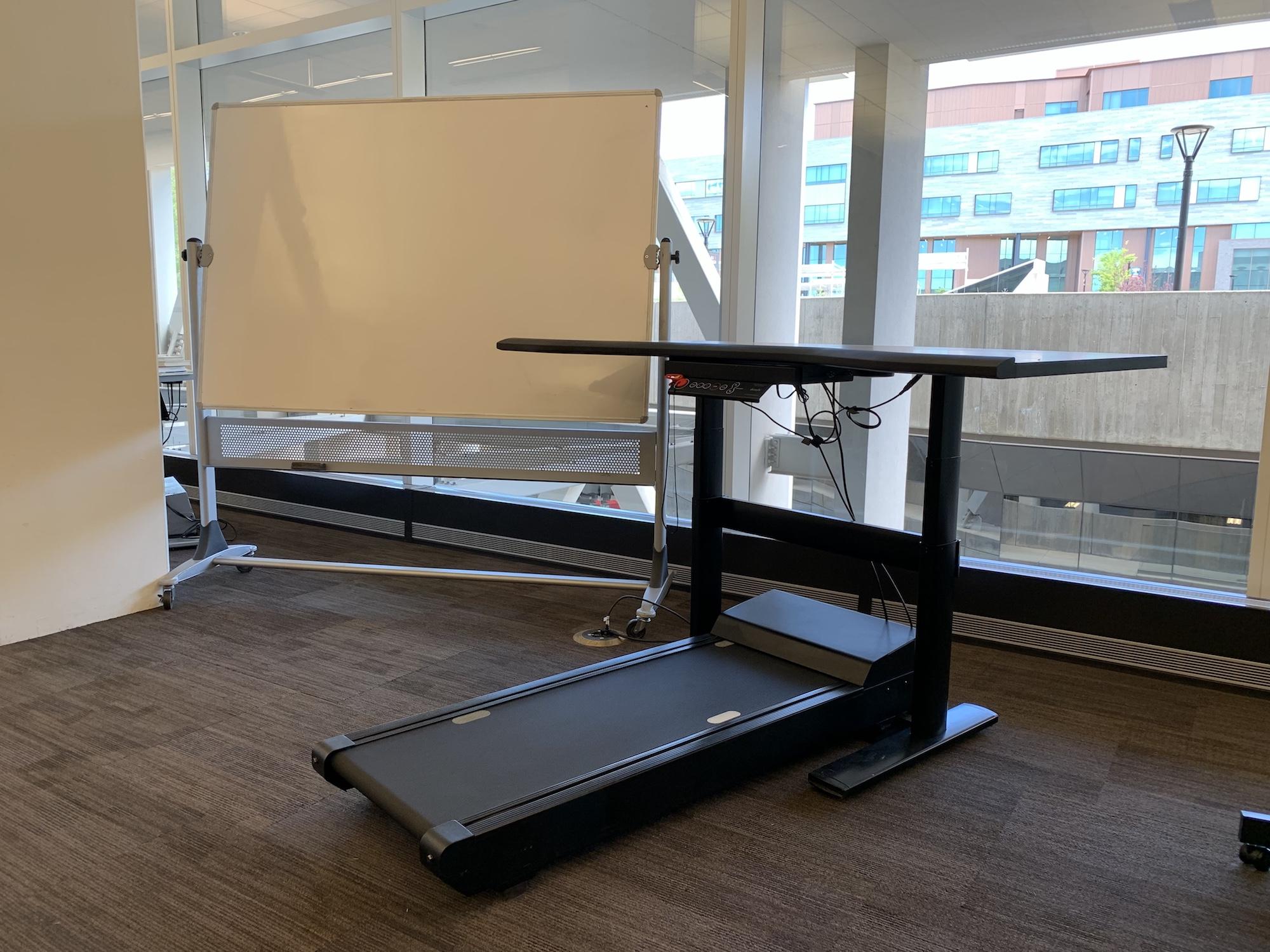 A treadmill desk and whiteboard.