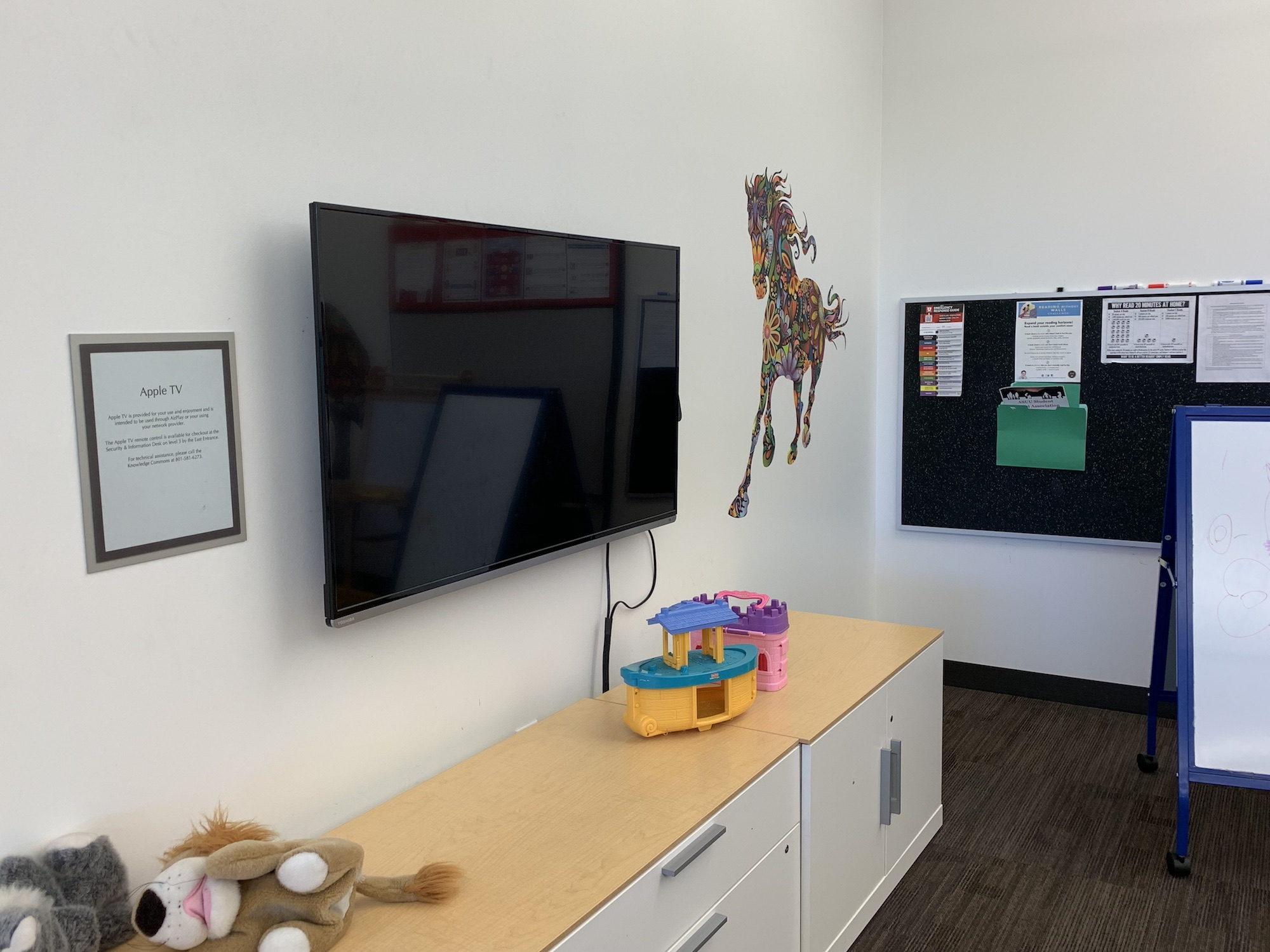 The TV inside of the family reading room with a horse wall graphic next to it.