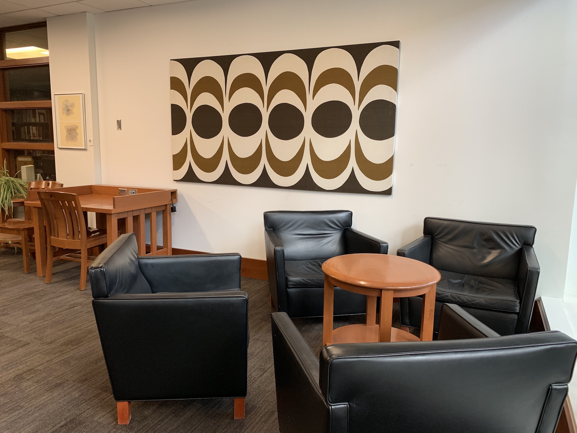 A group of four black chairs in the Fine Arts Library with a modern painting hung on the wall.