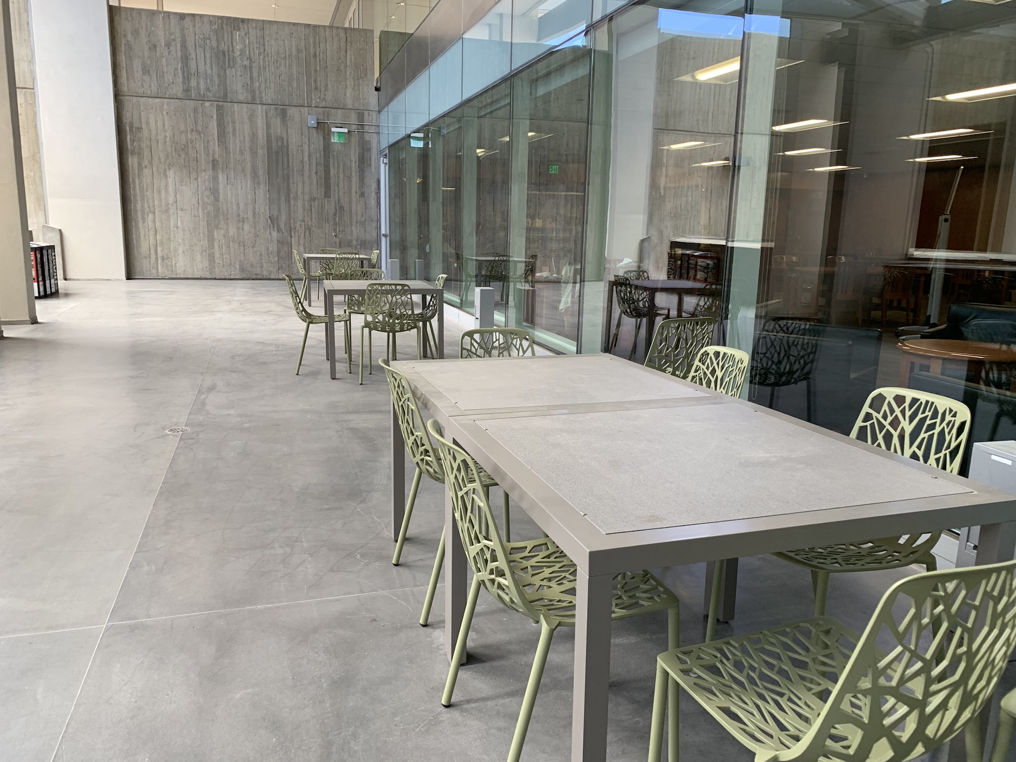 Outside tables and chairs next to windows in the courtyard.