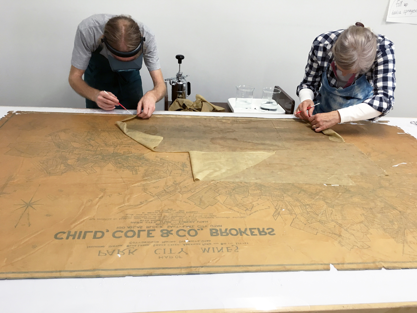 Jeff and Annabelle removing adhesive residues from the back of the map.