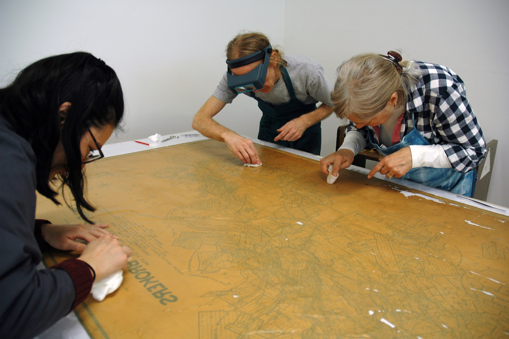 Stacey, Jeff and Annabelle removing adhesive residues from the back of the map.