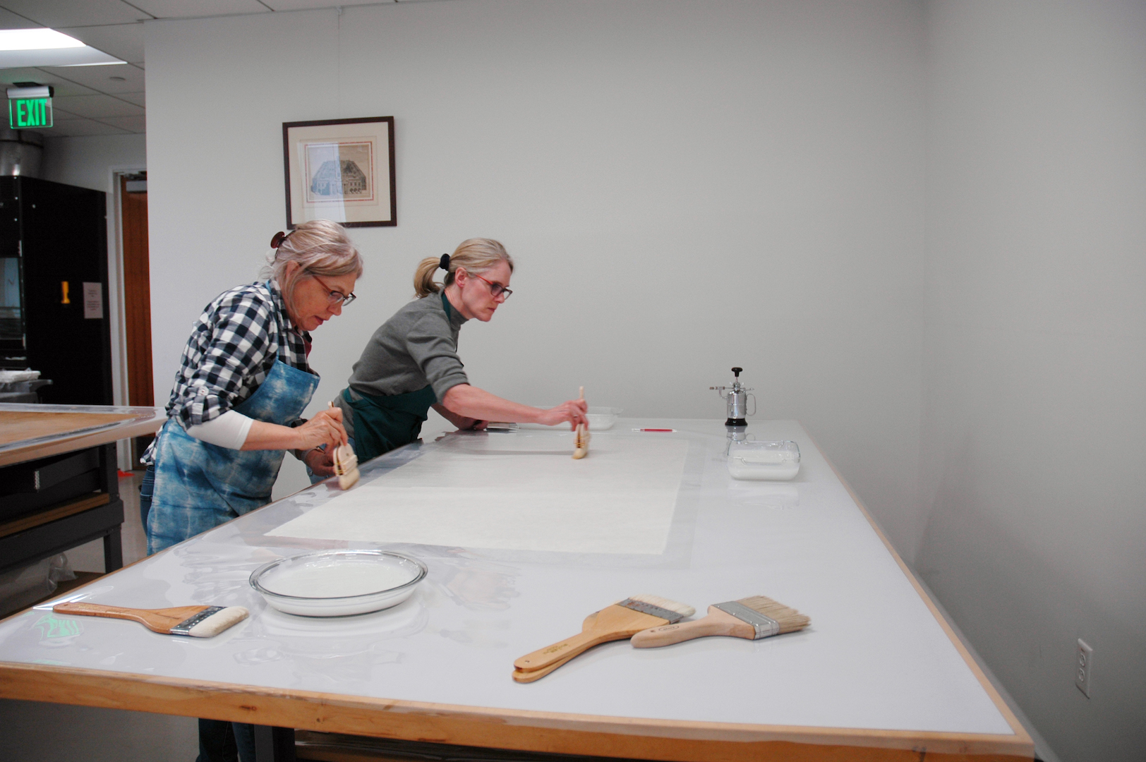 Annabelle and Susan pasting up the lining paper with traditional Japanese paste brushes.
