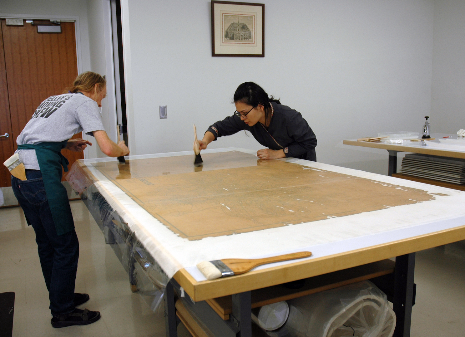 Jeff and Stacey using traditional Japanese smoothing brushes to remove air bubbles and ensure good adhesion between the lining and the map.