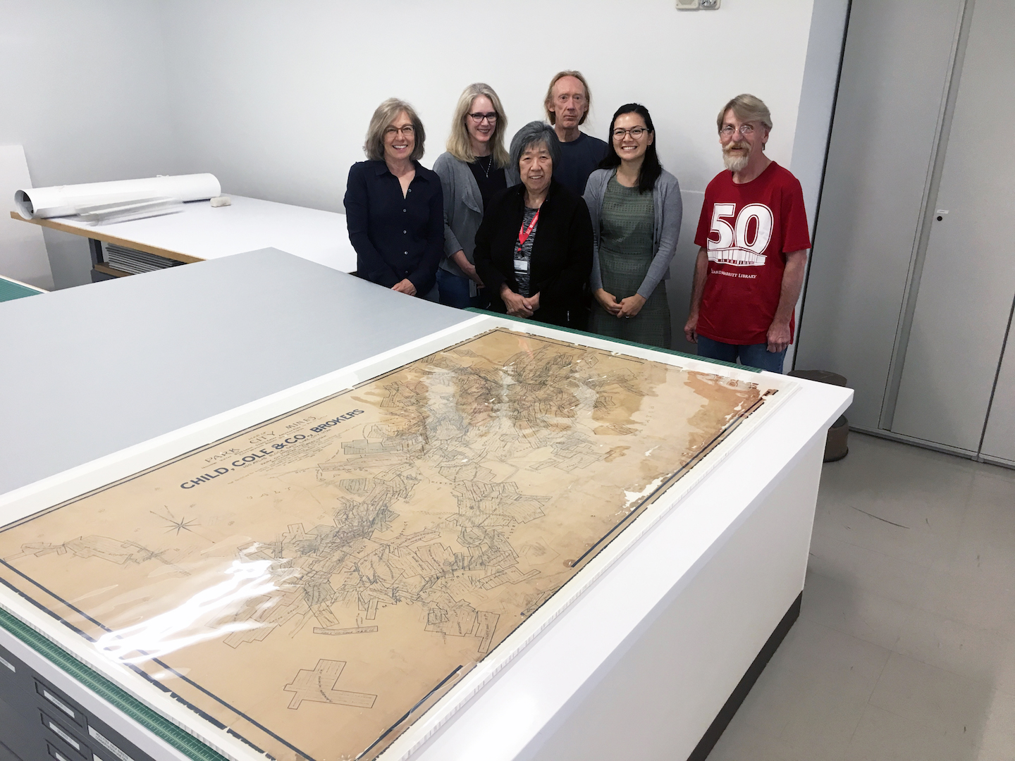 The map in its protective storage folder, and the Preservation team that conducted the treatment. From left: conservation technician volunteer Annabelle Shrieve, conservation technician Susan Schlotterbeck, book conservator Jeff Hunt, Conservator of works on paper Stacey Kelly, Conservation technician Frank Pester, and (front) Conservation Assistant Peggy Leo.