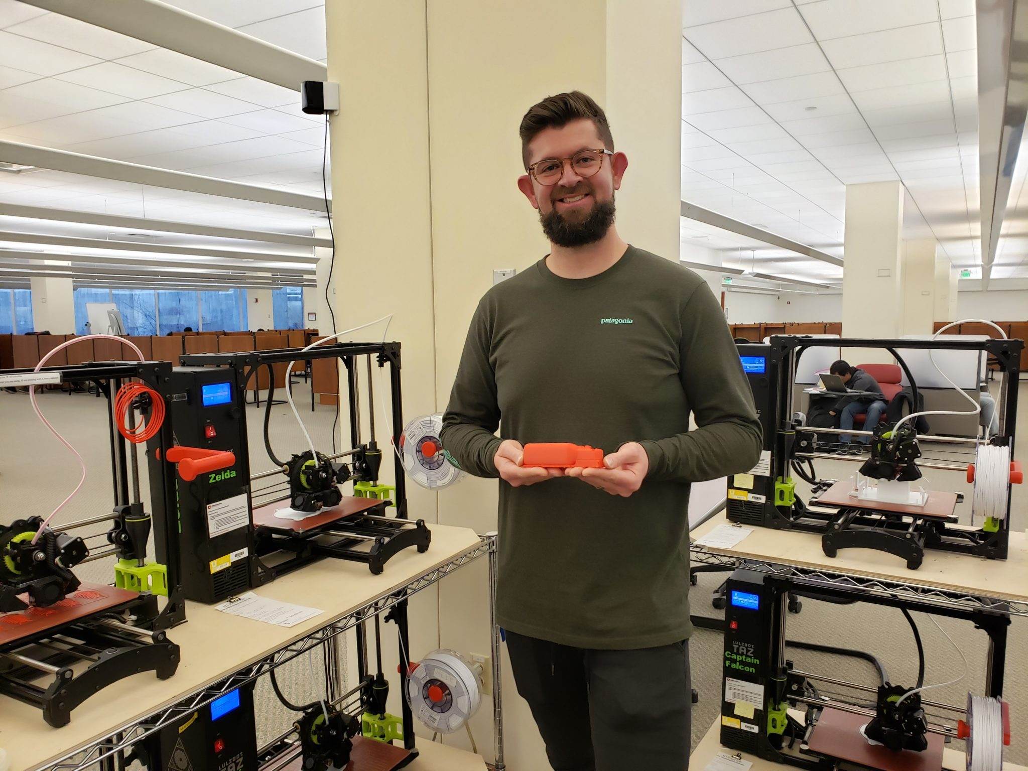 man smiling in front of 3D printer