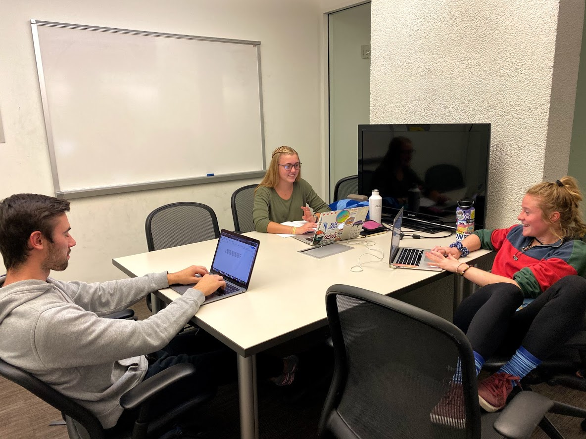 three students smiling while working on laptops in a private study room