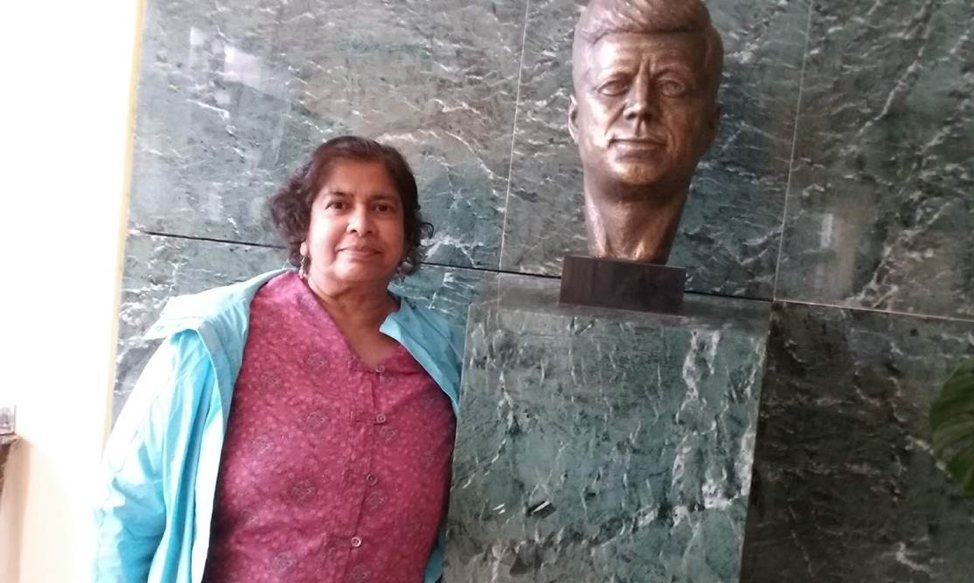 Marie standing next to a statue bust of JFK.