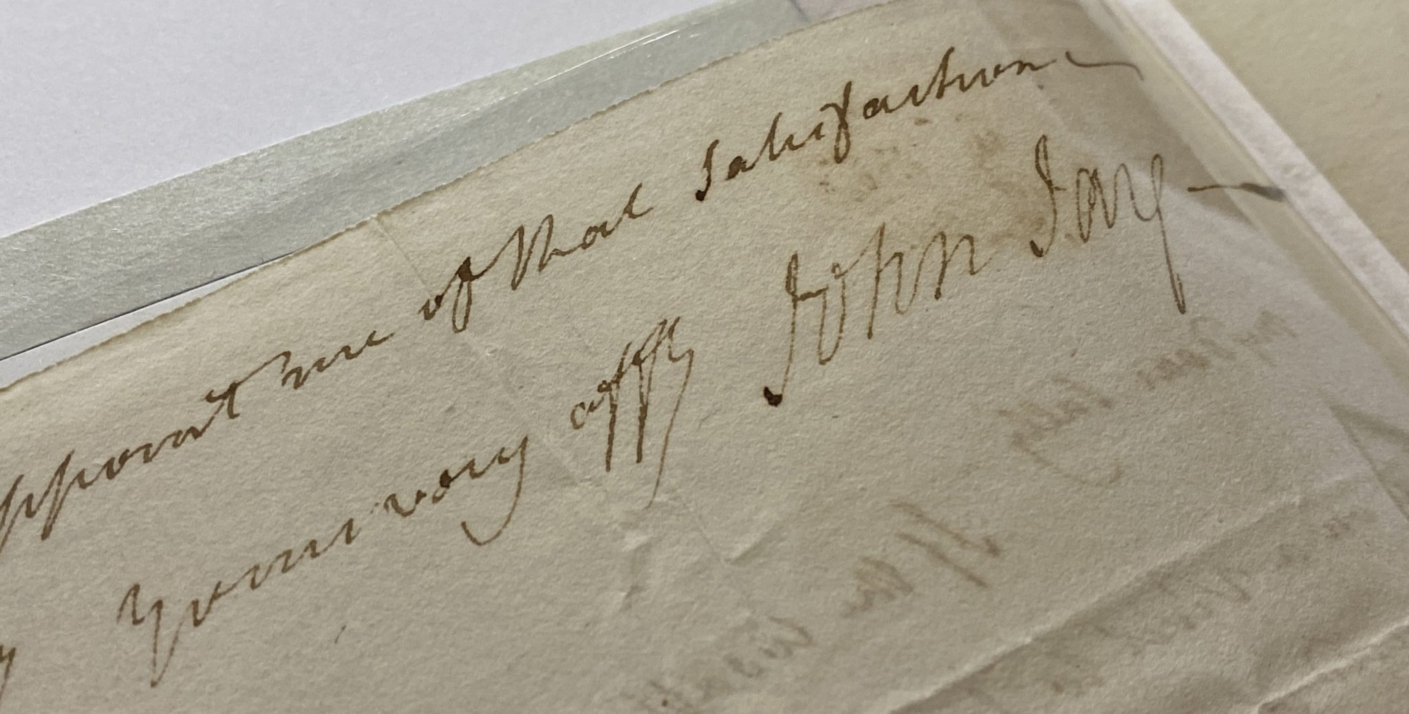 A close up of a signature by justice John Jay. The paper looks old but is preserved in a plastic.