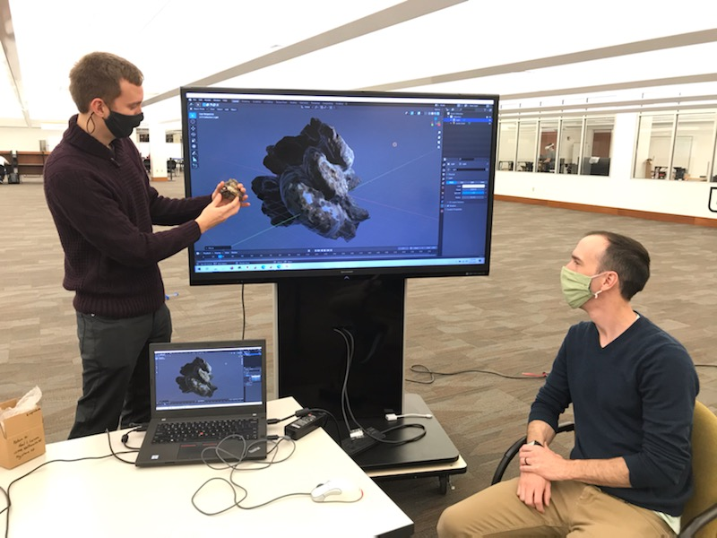 Photograph of Dr. David Peterman explains the details of a scanned model.