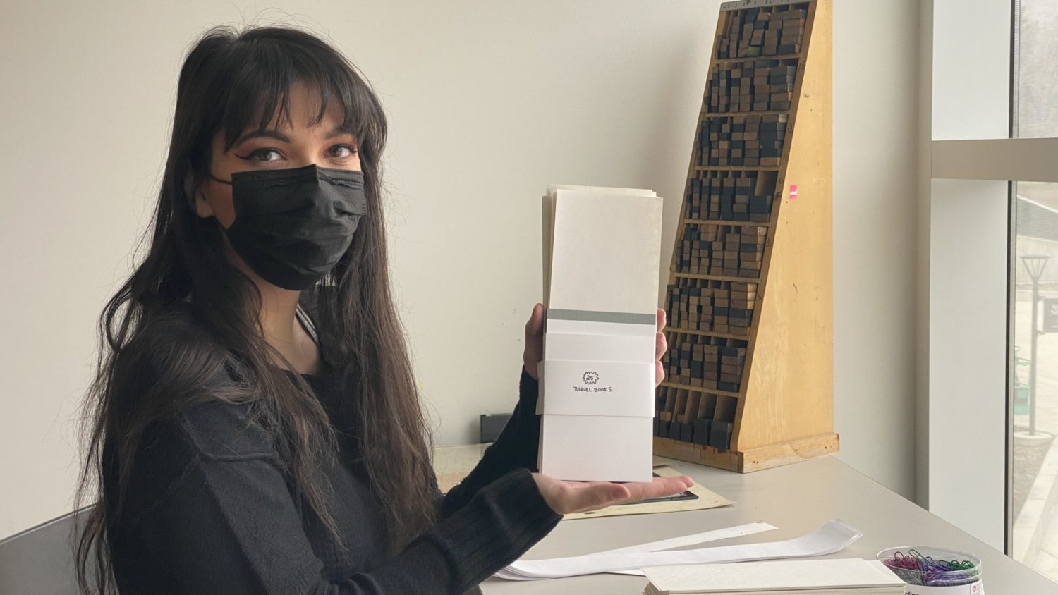 Victoria Dennis holding one of the packets she assembles for the Book Arts community programming.