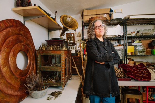 beth krensky standing in an art studio with several art supplies